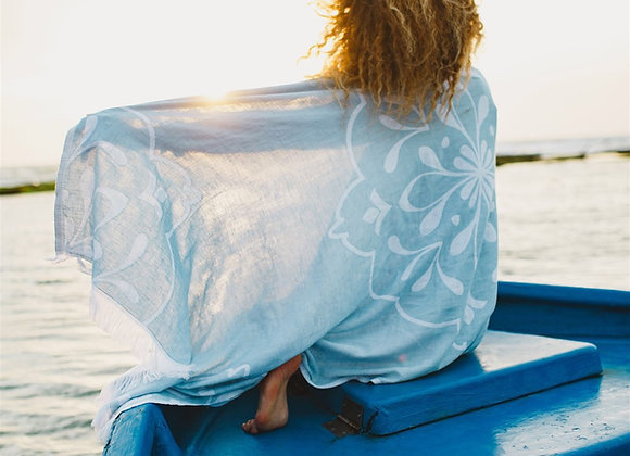 בחורה עם הגב למצלמה מתעטפת במגבת חוף כחולה ויושבת על סירה