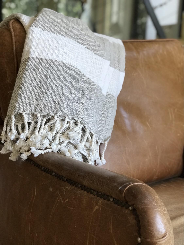 שמיכת פשתן מקופלת ומונחת על הספה