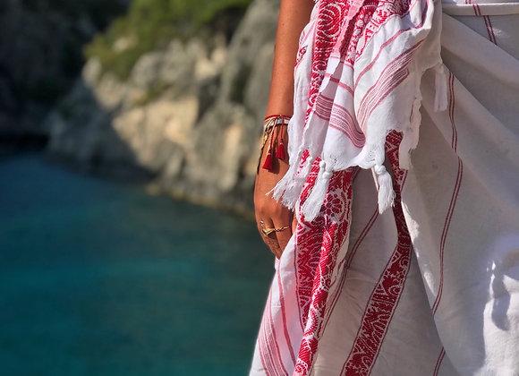 אישה קשרה מגבת חוף בצבע אדום לבן מסביב למותן