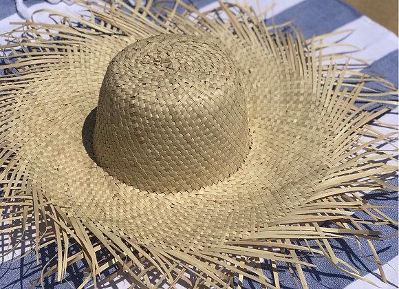 כובע קש ברמודה על מגבת חוף כחולה לבנה