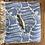 מחזיק מפתחות בצורת דג מונח על מגבת כחולה