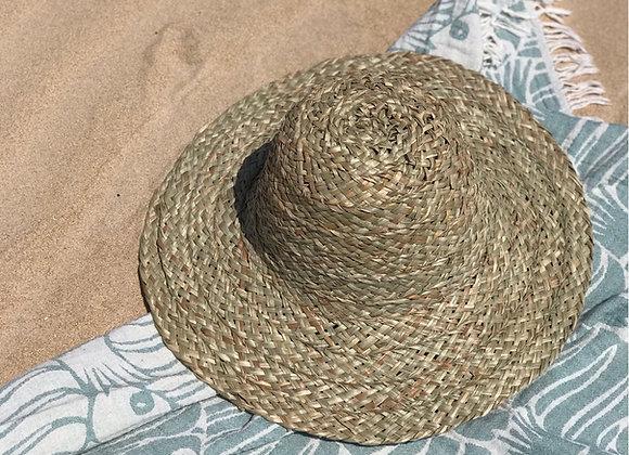 כובע קש מונח על מגבת בחוף