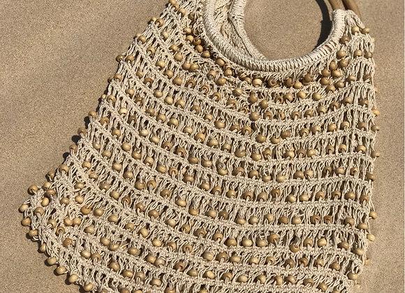 תיק קש דגם קוקוס מונח על החול