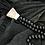 שרשרת חרוזי עץ בשילוב קונכייה גדולה מונחת על סדין שחור