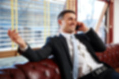 happy-businessman-sitting-and-talking-on
