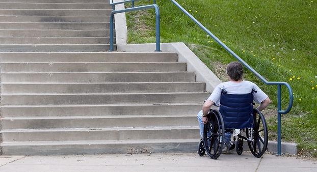 man in a wheelchair faces a large stairw