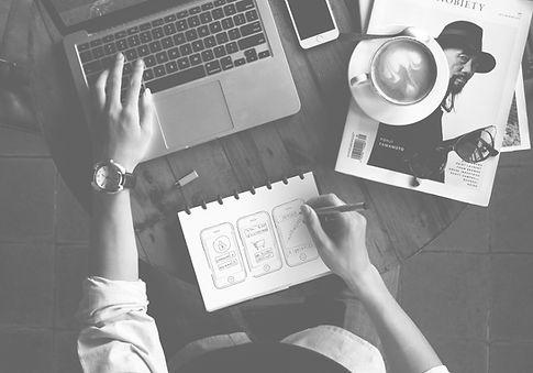 Pessoa trabalhando no notebook e anotando no caderno