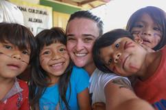 A fotógrafa Isadora Manerich em selfie com as crianças da Aldeia Tava'í.