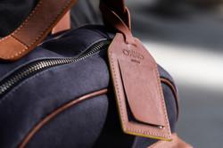 Etiquette de voyage en cuir attaché au sac à dos