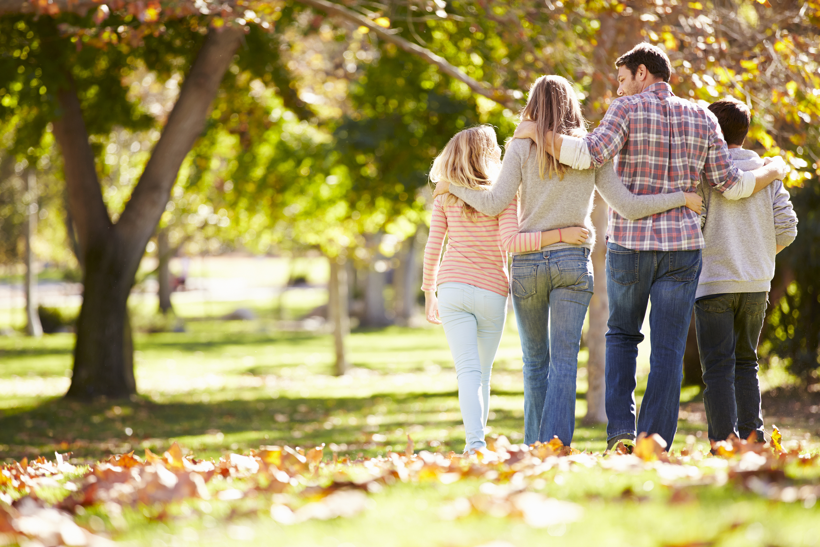 Rear View Of Family Walking Through Autumn Woodland.jpg