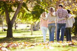 Rear View Of Family Walking Through Autumn Woodland.jpg