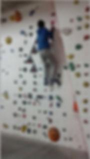 תלמיד הכיתות התקשורתיות על קיר טיפוס