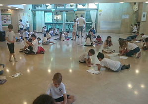 תלמידי היסודי מציירים על הרצפה