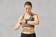 fit-woman-looks-attentively-smartwatch-g