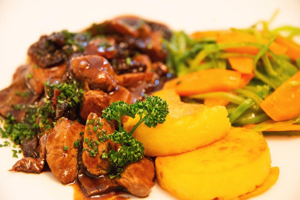 sliced beef with mushroom sauce, polenta and vegetables