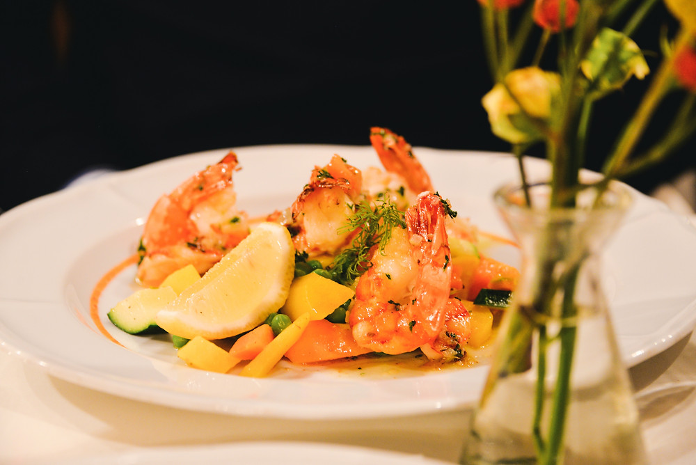 fried king prawns with fresh herb butter and market vegetables