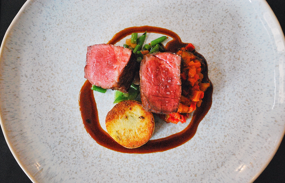 A pink roasted beef fillet on ratatouille