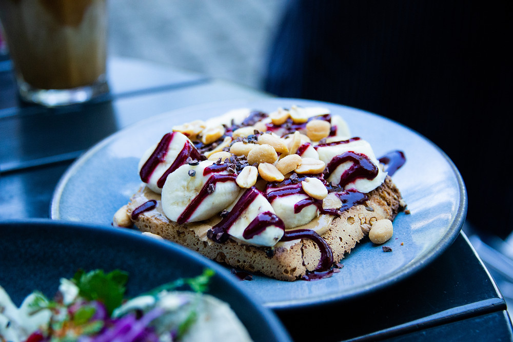 peanut butter banana toast with raspberry cherry sauce and cocoa nibs,