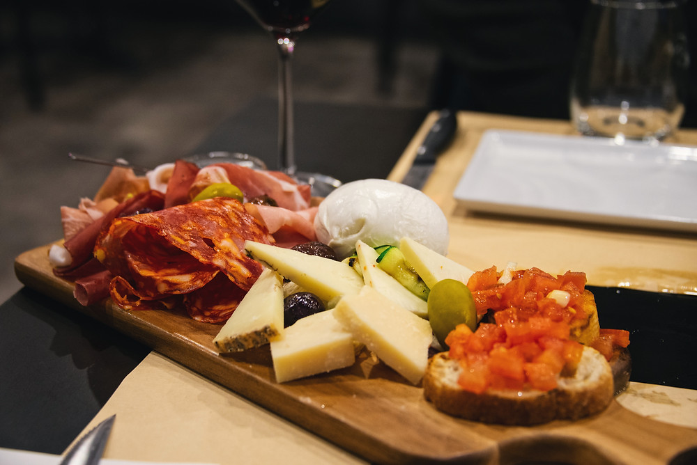antipasti platter with selected delicacies such as various cold cuts, cheeses and honey, burrata, bruschette, olives