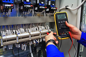 engineer tests the industrial electrical circuits with a multimeter in the control termina
