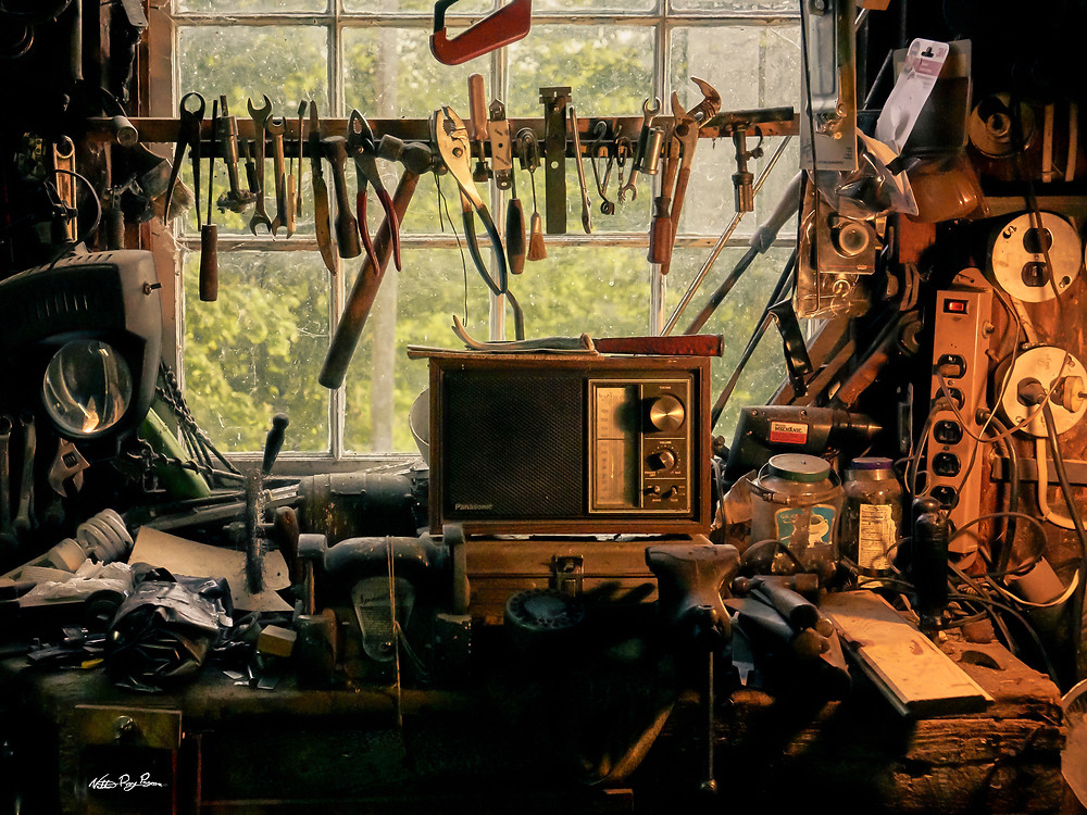 Old workbench, radio, and tools bathed in orange light with deep shadows and a window looking out into summer