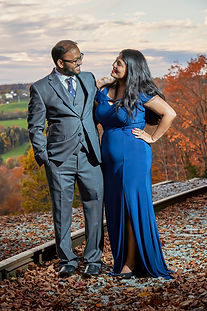 A young couple pose for their engagement session along an old railroad overlooking an autumn valley.