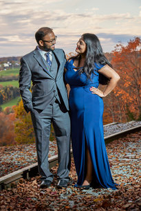 A finely dressed young couple pose over a valley of autumn color and traintracks.