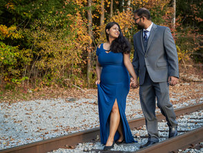 A young couple enjoy each others company as they walk down an old train track.