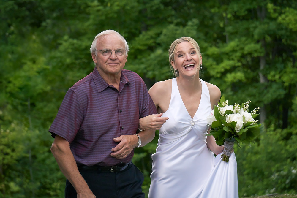 Bride and Father walk arm in arm on her wedding day