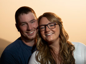 A young couple pose for a close up portrait with the warm glow of the sun behind them.
