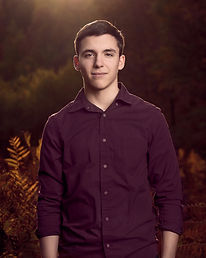 A young man poses for his senior portrait. Warm dark tones and sunlight accent the image.