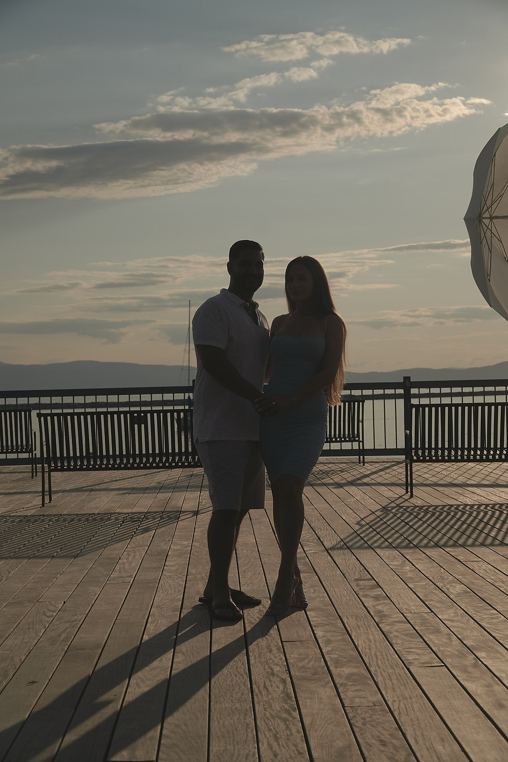 A couple drenched in shadows stands on a pier. In the upper right hand corner you can see a flash umbrella that is dark.