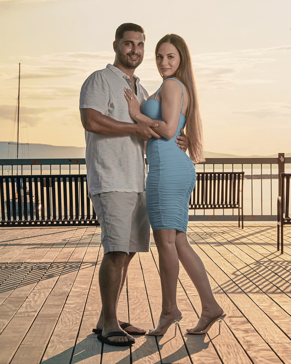A beautiful woman poses with her fiancé on a pier in the evening glow of the fading sun.