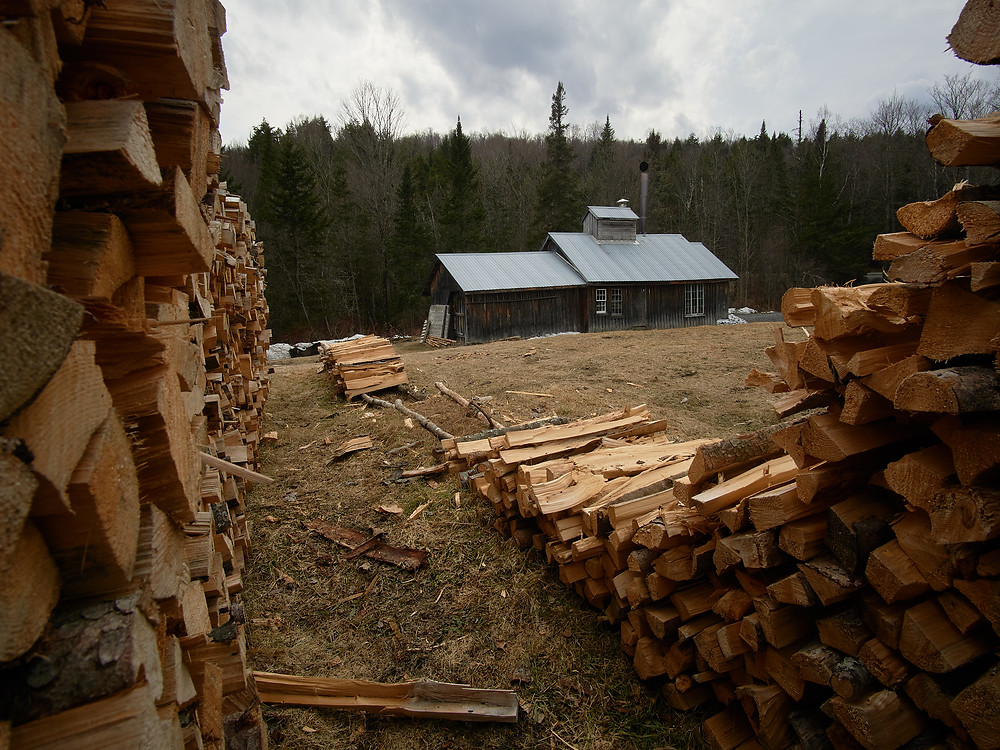A wood pile frames a sugar house in Central Vermont