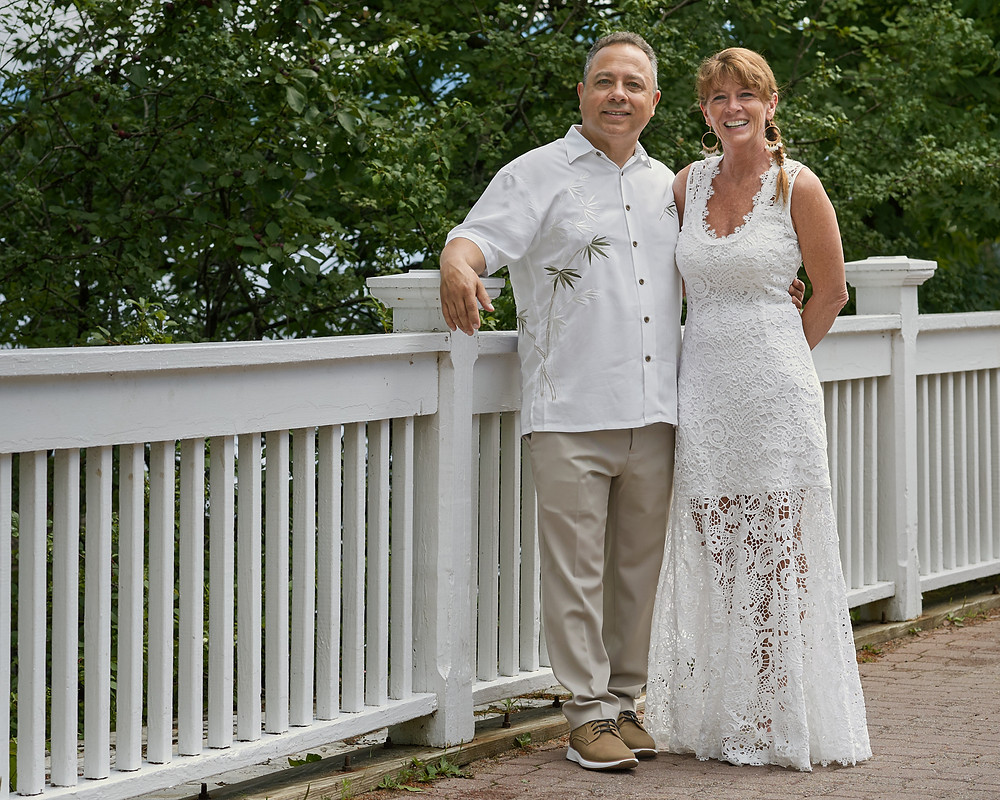 Bride and groom pose against a white fence on their wedding day.