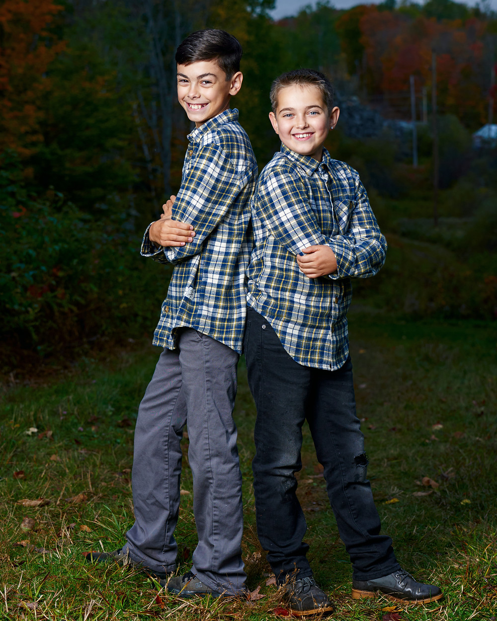 Two brothers stand back to back with mischievous grins and arms crossed.