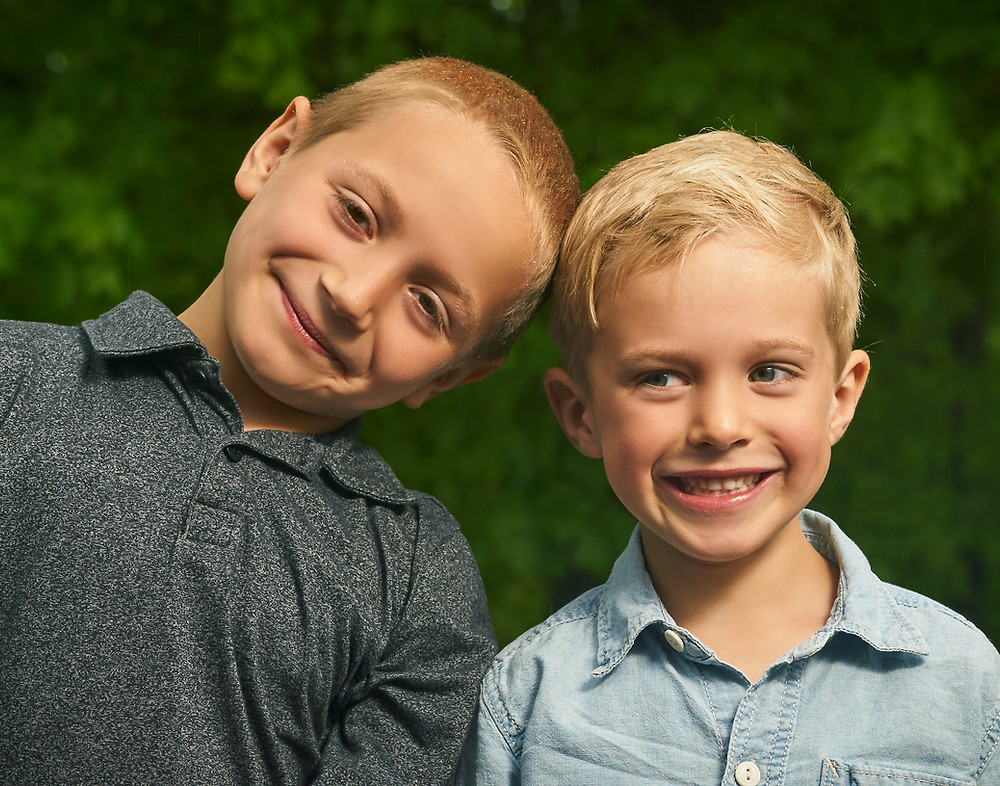Two brothers stand shoulder to should with impish grins as one peers at the other out of the corner of his eye.
