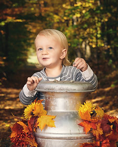 A blonde boy peers from around an old milk carton decorated for autumn. A forest path as background.