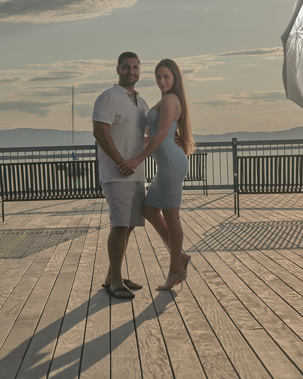a couple poses on a pier. In the upper right hand corner you can see a flash umbrella lit helping expose the image properly.