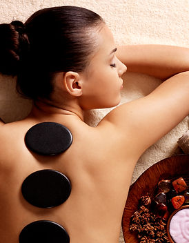 Young woman having stone massage in spa