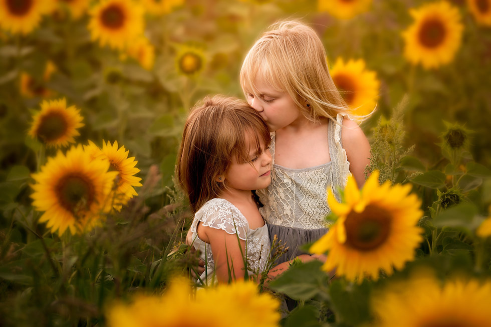 sisters in the sunflowers at sunset golden hour