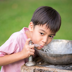 Child drinking from a public drinking fountain outside.