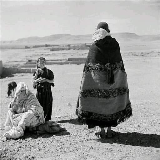 Homme juif de dos  vêtu de l'akhnif dont la décoration de demi-lune rouge est tournée vers l' intérieur afin de le distinguer du reste de la population musulmane. Les mêches de laine, extérieures au décor, apparaissent sur le bas. Il porte sous ce manteau à capuche tissé la djellaba noire.