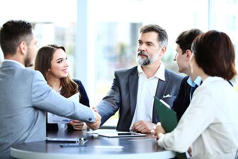 Cinco personas alredeor de una mesa de reunión. Tres hombres y dos mujeres. Dos hombres se estrechan la mano y uma mujer sonríe.