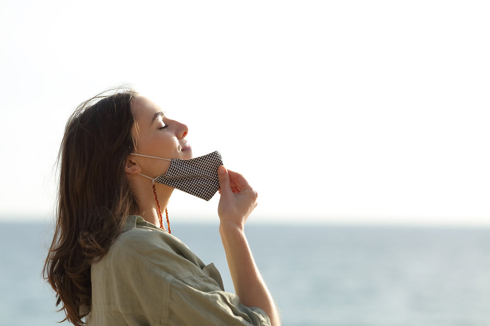 Side view portrait of a woman breathing deep fresh air relieving taking off mask due covid
