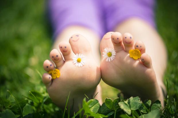 Ребенок без детской обуви отдыхает на травке.