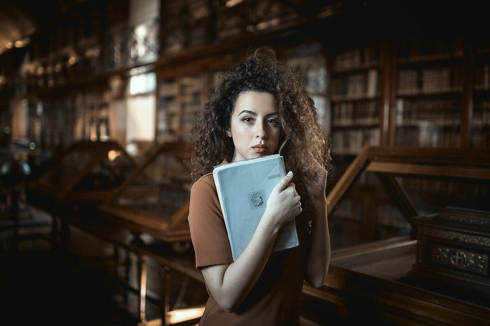 woman_in_white_dress_holding_book-scopio