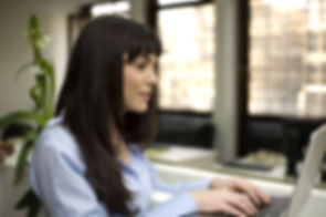 This photograph shows a young woman in the foreground typing on a laptop computer in an office.