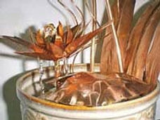 Copper Sculpture of flower and leaves in vase