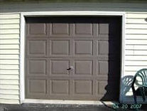 Single brown garage door that is chalky and oxidized
